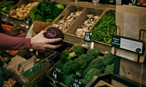 Shopper choosing vegetables in Morrisons with paper bags on display