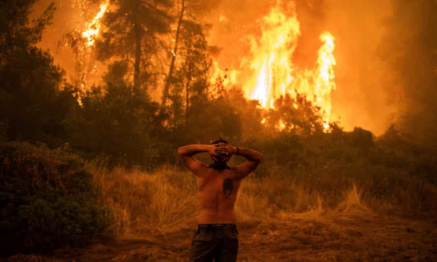 A resident watches a wildfire on Evia island, Greece, as the region endures its worst heatwave in decades.