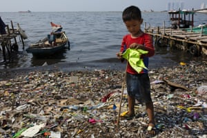 A boy plays with a makeshift flagpole on a beach covered in plastic waste in Indonesia.