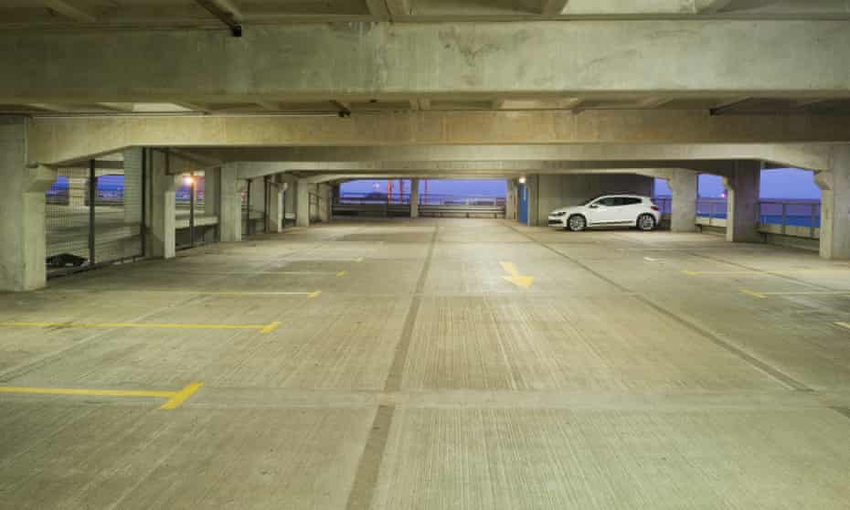 A single white car at dusk in an otherwise empty multi-storey car park