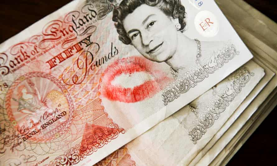 A pile of £50 notes with the top one featuring a lipstick mark