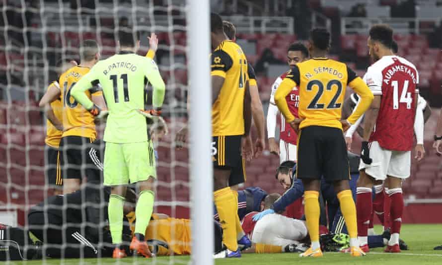 Wolves forward Raúl Jiménez lies on the ground after a clash of heads with David Luiz. Jiménez was taken to hospital, where he is conscious and responding to treatment.