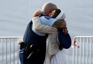 A relative of a victim hugs a police officer during a burial ceremony in Christchurch