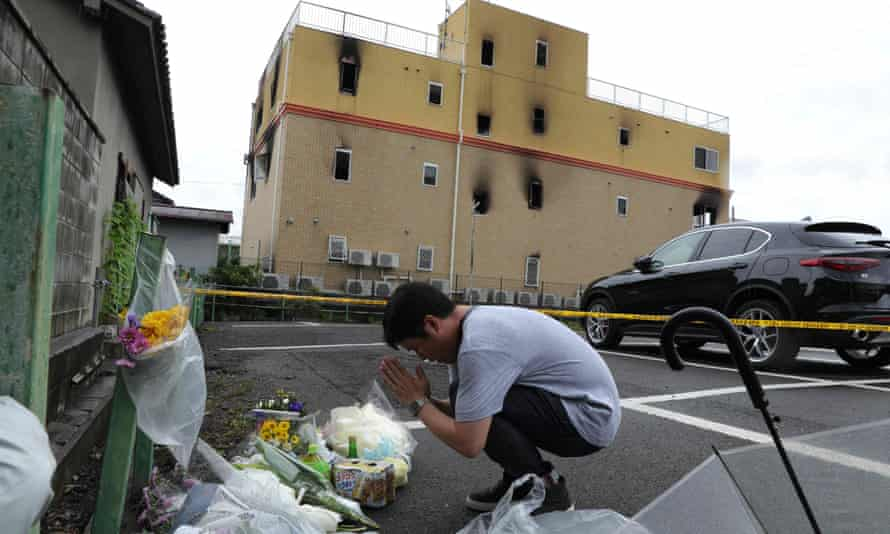 file photo taken on July 19, 2019 shows a man praying next to flowers and tributes laid at the scene where over 30 people died in a fire at an animation company building in Kyoto