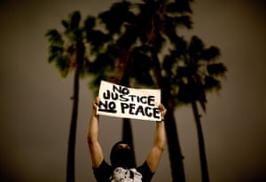 A demonstrator holds up a sign - no justice, no peace - in Los Angeles