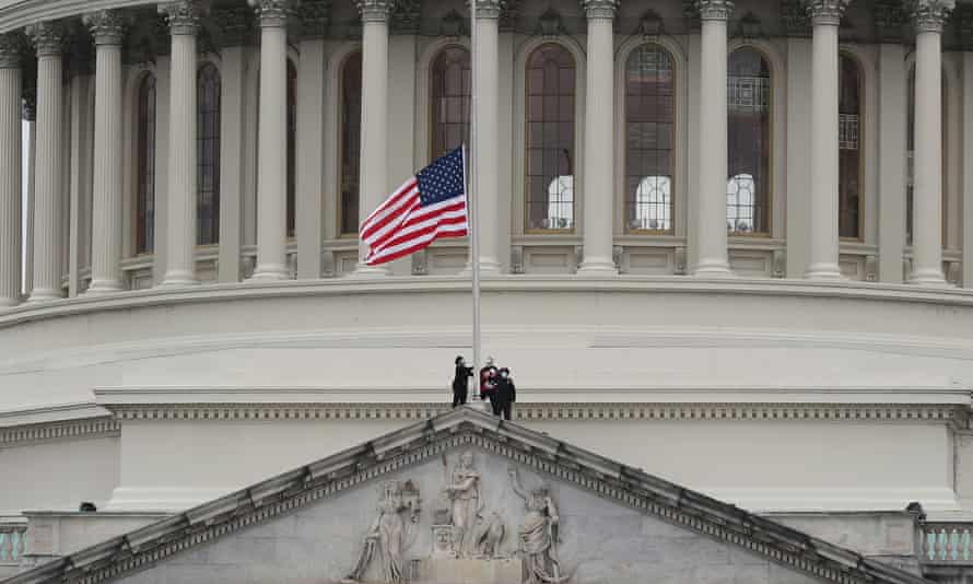 The American flag is lowered to half-mast on the Capitol following the death of a police officer in the attack on the building on 6 January.