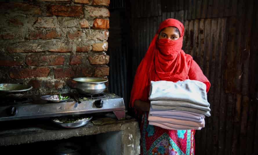 A garment worker holds sweaters made in Bangladesh for an international brand.