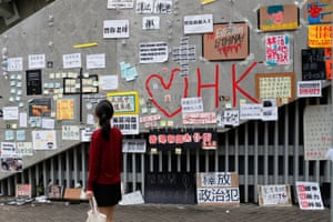 A passer-by looks at notes and placards with messages of support for the protest against the extradition bill in Hong Kong.