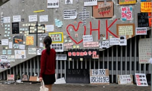 Passer-by looks at notes and placards with messages of support for the protest against the extradition bill in Hong Kong.