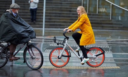 Helen Pidd riding a Mobike in rainy Manchester.