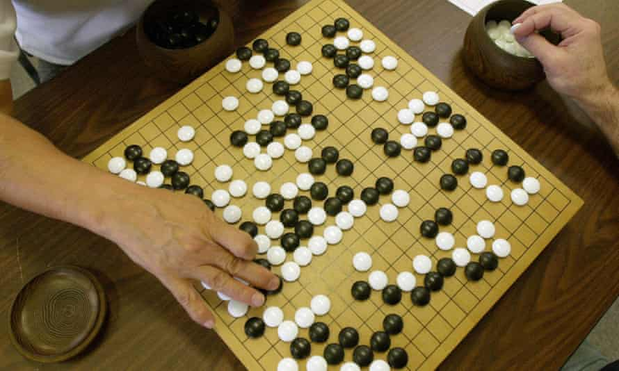 A player places a black stone while his opponent waits to place a white one as they play Go