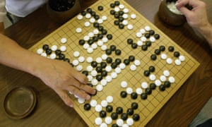 A player places a black stone while his opponent waits to place a white one as they play Go, a game of strategy.