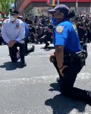 New York police officers kneel along with protesters after protesters said they asked them to do so, in this still frame obtained from social media video in Queens, New York, on Sunday.