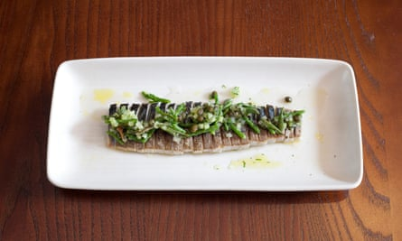 An oblong plate of mackerel tightly sliced and sprinkled with cucumber and capers