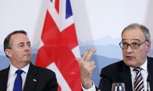 Liam Fox looks on as Guy Parmelin gestures