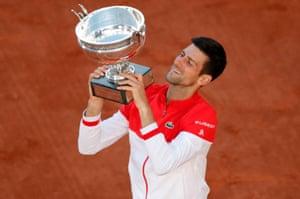 A beaming Novak Djokovic celebrates with the trophy.