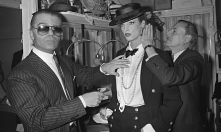 Lagerfeld prepares a model backstage ahead of his debut Chanel show in 1983.