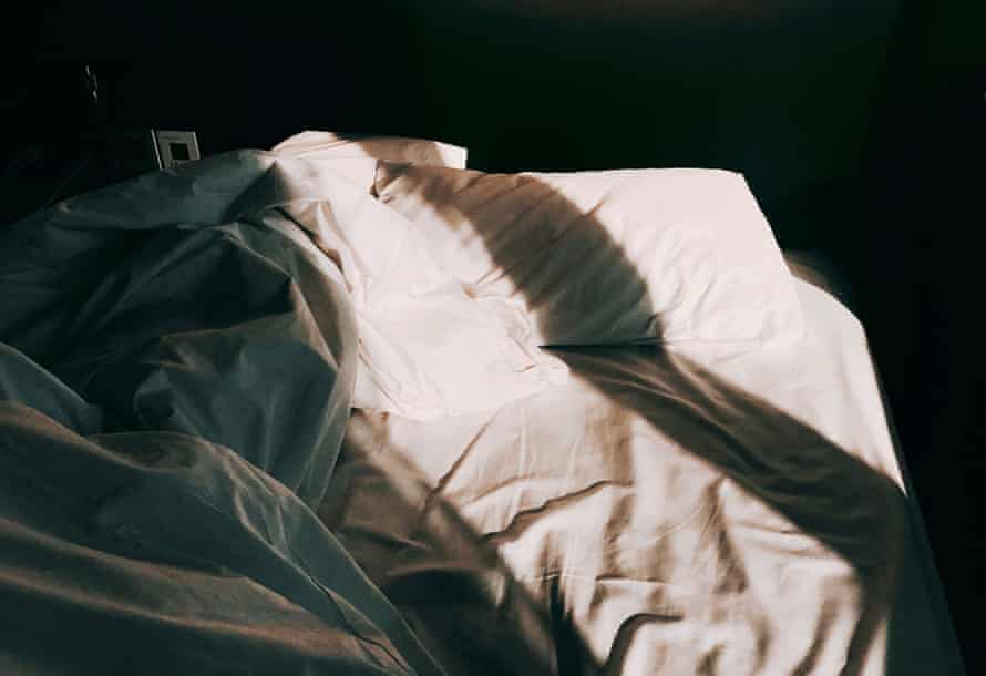 An unmade bed with morning light.
