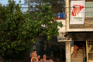 In Havana a family wait for the arrival of their famous visitors, next to a banner with the tongue image made famous by the Rolling Stones