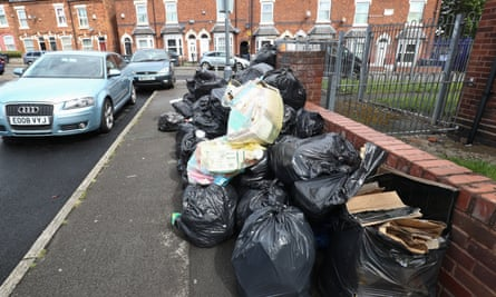 Rubbish bags piled high on a pavement in Birmingham
