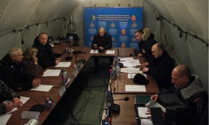 Vladimir Putin (centre) attends an emergency meeting about the collapse