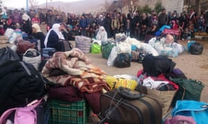 Syrians wait for the arrival of an aid convoy in the besieged town of Madaya, 11 January 2016