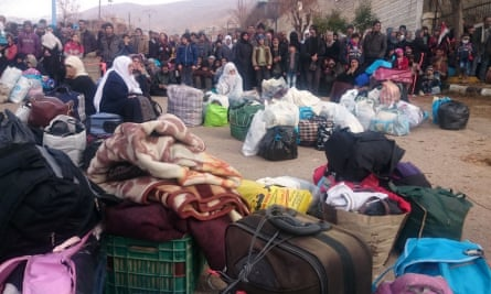 Syrians wait for the arrival of an aid convoy in the besieged town of Madaya.
