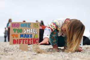 A girl plays on the beach in Falmouth during a protest by Cornwall Climate Youth Alliance in partnership with Fridays for Future and Climate Live