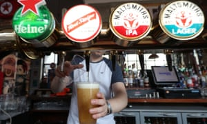 A barman serving takeaway drinks at a pub in London.