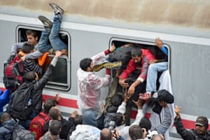 Migrants desperately try and board a train heading for Zagreb from Tovarnik station, Croatia