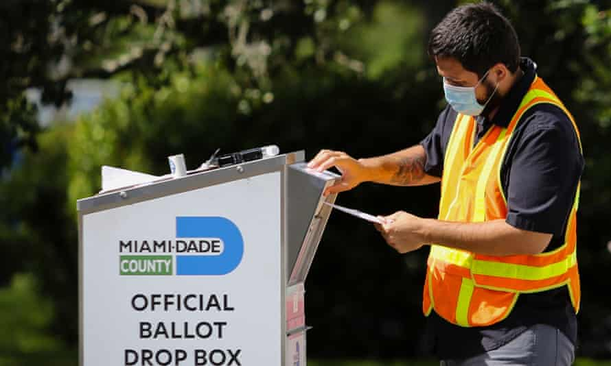 A poll worker places a ballot in a drop box at Miami-Dade county election department in Miami, Florida, on 3 November.