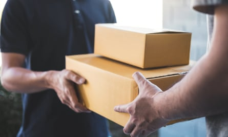 Midsection Of Delivery Person Giving Boxes To Young Man At Home