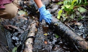 A woman shows crude oil from a well in Amazonian Peru.