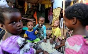 Mogadishu, Somalia. Children share a bowl of rice outside their family's makeshift shelter at the Al-cadaala camp