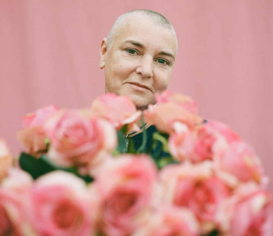 Head shot of Sinéad O'Connor against pink background, with a bunch of pink roses in front of her