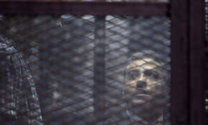 Baher Mohamed, left, and Mohamed Fahmy listen to their verdict in a soundproof cage in a courtroom in Tora prison in Cairo. Their initial 2014 conviction said the journalists had been brought together 'by the devil' to destabilise Egypt.