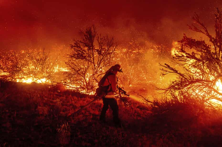 A firefighter battles the Dixie fire as it jumps Highway 395 in Lassen County, California, last month.
