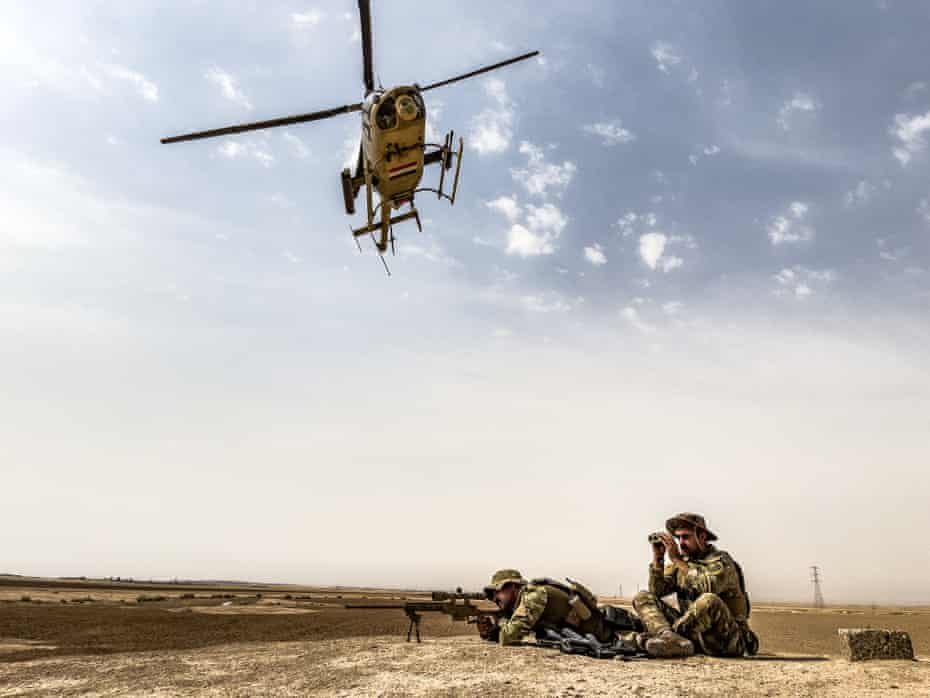 An Iraqi special forces sniper team takes a position over a hill, during search operations targeting Islamic State militants, south of the city of Kirkuk.