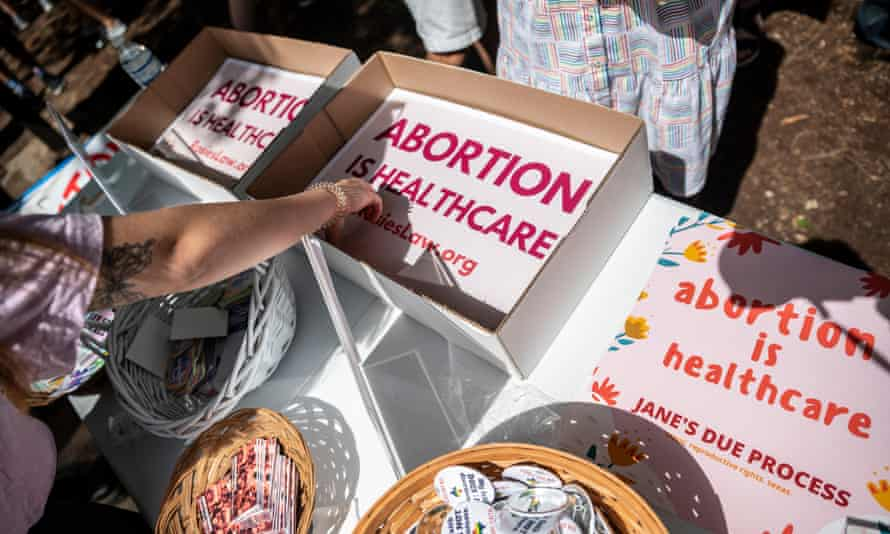 People grab signs reading 'Abortion is healthcare' at. a protest outside the Texas state capitol in Austin on 29 May.