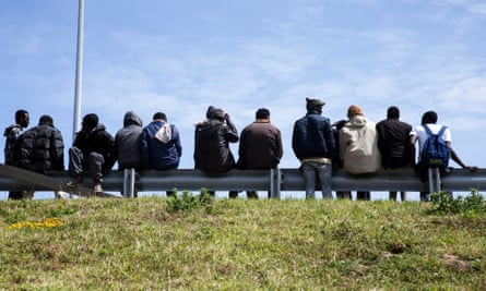 Refugees in Calais wait for lorries heading to Britain that they can jump on to, June 2015.