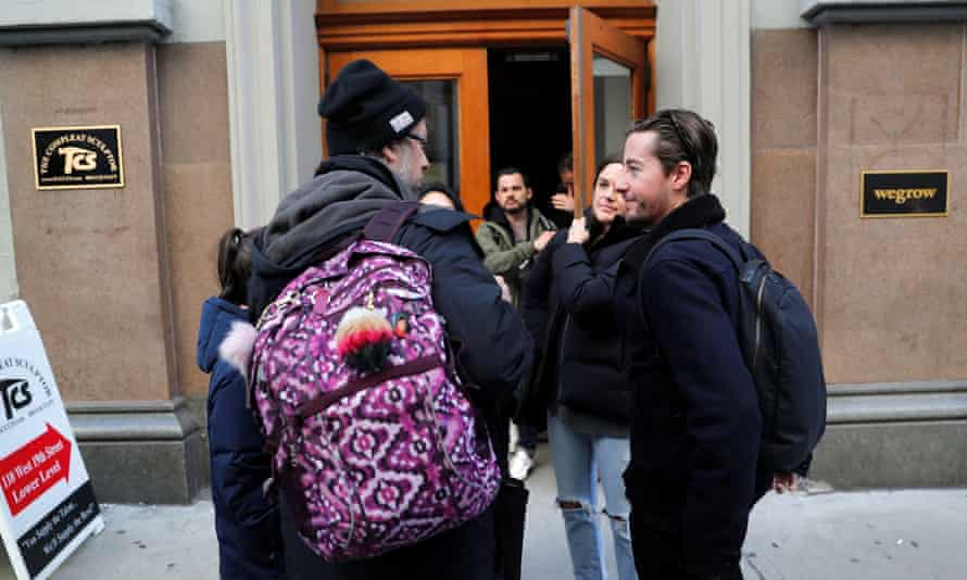 Laid-off WeWork employees gather on sidewalk outside WeWork corporate headquarters in Manhattan, New York.