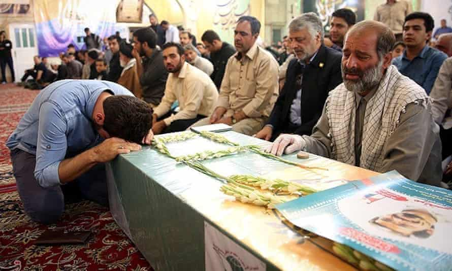 Mourners gather around the bodies of Iranians killed in Syria, during their funeral in Mashad, Iran