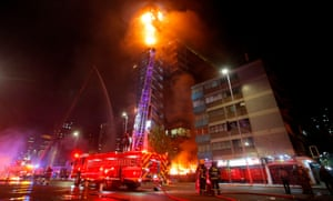 Flames engulf the iconic Enel building in downtown Santiago on Friday.