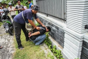 Riau, Indonesia A plain-clothed police officer arrests an inmate