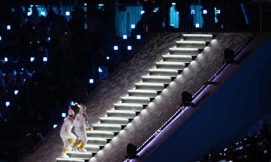 Ice hockey players from North and South Korea climb the stairs with the Olympic torch.