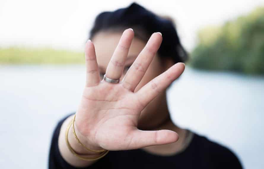 Young woman hiding face with hand by lake