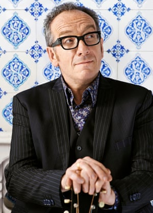 Elvis Costello, wearing glasses, in a jacket and waistcoat, his hands on the top of a guitar, smiling quizically