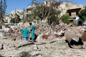 Syrian people inspect the pit around the Sahra hospital after a barrel bomb strike by Syrian regime forces