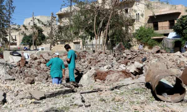 People inspect the pit around the Sahra hospital after a barrel bomb strike on 1 October.
