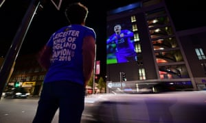 A Leicester City football fan looks up at a large projection of an image of Leicester City's striker Jamie Vardy on the side of a building